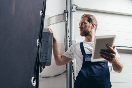 Photo for Low angle view of male bearded repairman with digital tablet checking electric box - Royalty Free Image