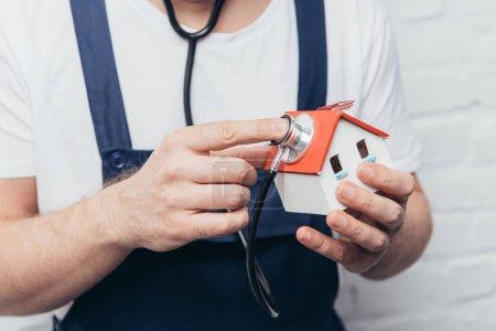Photo pour Plan recadré de l'artisan vérifiant chiffre de la maison par stéthoscope, concept d'inspection à domicile - image libre de droit