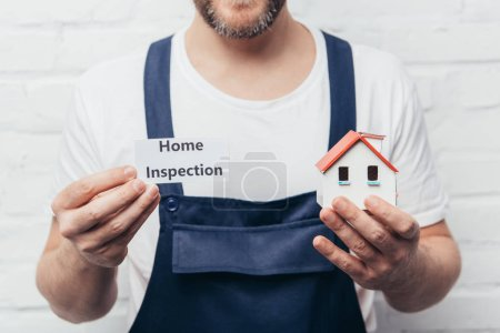 cropped image of male craftsman showing house model and card with lettering home inspection