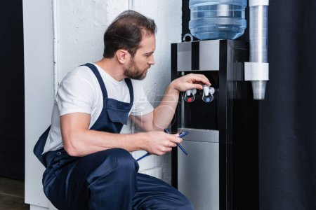 Photo pour Réparateur avec presse-papiers vérifier refroidisseur d'eau cassé - image libre de droit