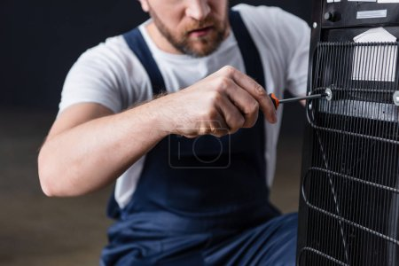 Photo for Cropped shot of male craftsman repairing water cooler with screwdriver - Royalty Free Image