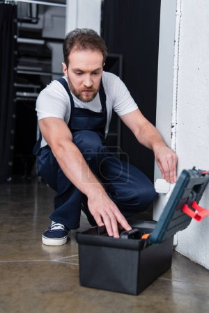 Photo for Electrician in working overall taking tools from toolbox during repairing of plug socket - Royalty Free Image