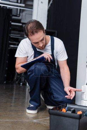 Photo pour Adulte électricien masculin avec presse-papiers prise de contrôle - image libre de droit