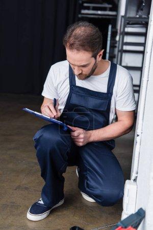 Photo pour Barbu mâle électricien écriture dans presse-papiers près de prise de courant - image libre de droit