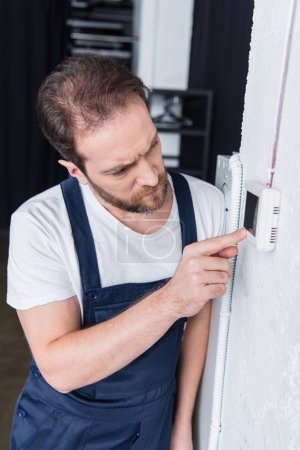 focused adult male handyman checking electrical panel
