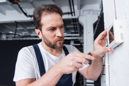 adult male craftsman fixing electrical panel by screwdriver
