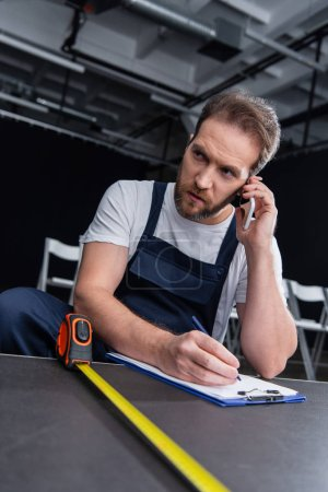 Photo for Male handyman talking on smartphone and writing in clipboard while measuring floor - Royalty Free Image