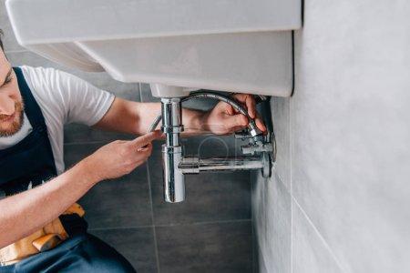 Photo pour Vue partielle du plombier masculin dans le travail évier de fixation globale dans la salle de bain - image libre de droit