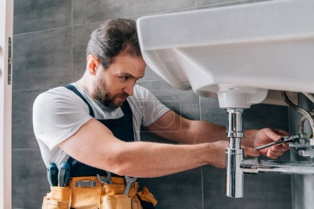 Photo pour Plombier masculin concentré dans le travail évier de fixation globale dans la salle de bain - image libre de droit