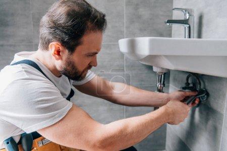 Photo pour Plombier masculin adulte dans le travail évier de fixation globale dans la salle de bain - image libre de droit