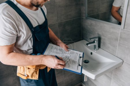 Photo pour Vue partielle du mâle plombier avec toolbelt écrit dans le presse-papiers d'évier cassé dans la salle de bain - image libre de droit