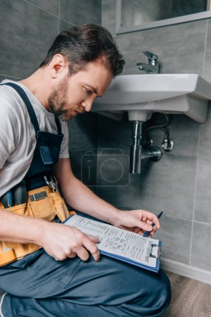 bearded male plumber with toolbelt writing in clipboard near broken sink in bathroom