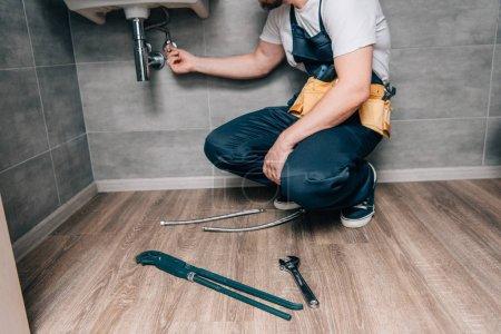 cropped shot of male plumber with toolbelt repairing sink in bathroom