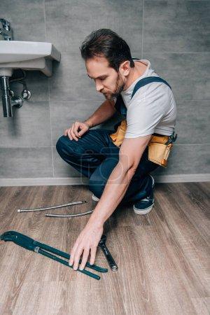 adult male plumber taking gas wrench for repairing broken sink in bathroom