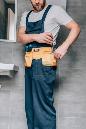 partial view of male plumber putting wrench in toolbelt in bathroom