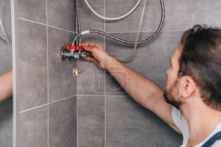 selective focus of male plumber repairing electric boiler in bathroom