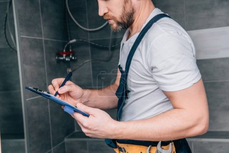 partial view of plumber writing in clipboard and checking electric boiler in bathroom