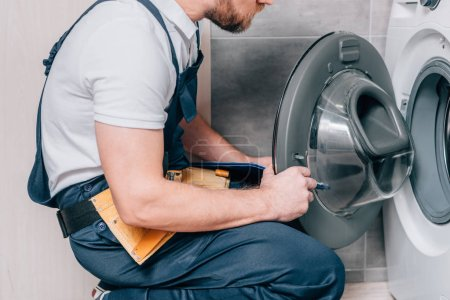 cropped shot of handyman with toolbelt and clipboard checking washing machine in bathroom