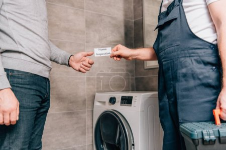 abgeschnittenes Bild eines männlichen Heimwerkers, der dem Besitzer im Badezimmer eine Karte mit Schriftzug gibt