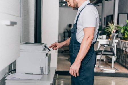 Photo pour Image recadrée de homme bricoleur réparation photocopieuse dans le bureau moderne - image libre de droit