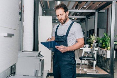Photo pour Bricoleur vérifiant la photocopieuse et l'écriture dans le presse-papier dans le bureau moderne - image libre de droit