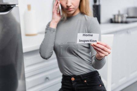 Photo pour Vue partielle de la jeune femme tenant la carte avec lettrage inspection de la maison et parler sur smartphone dans la cuisine - image libre de droit