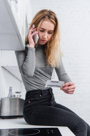 schöne junge Frau hält Karte mit Schriftzug nach Hause Inspektion und spricht auf dem Smartphone in der Küche