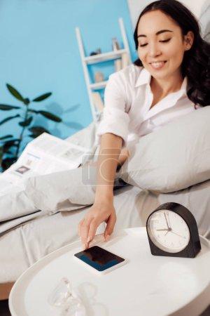 Photo pour Belle jeune femme souriante couchée au lit et cherchant un smartphone le matin - image libre de droit