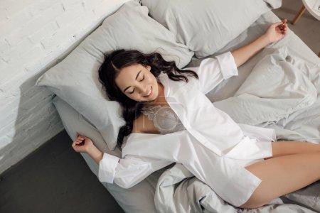 Photo pour Vue supérieure de belle fille asiatique heureuse en chemise blanche et soutien-gorge couché dans le lit - image libre de droit