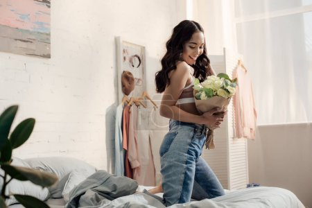 Photo for Happy attractive asian girl kneeling on bed and holding beautiful flower bouquet - Royalty Free Image