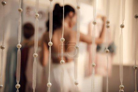 Photo pour Vue rapprochée des rubans blancs décoratifs avec perles et jeune femme choisir des vêtements dans l'armoire derrière - image libre de droit