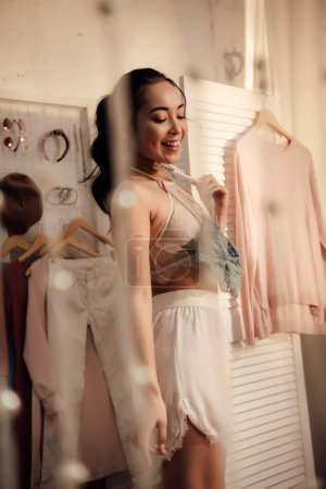 Photo for Beautiful smiling young woman choosing what to wear in wardrobe - Royalty Free Image