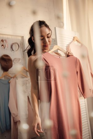 Photo for Beautiful smiling asian woman in underwear holding hanger with stylish dress in wardrobe - Royalty Free Image