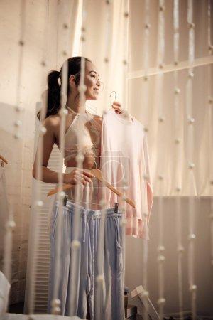 Foto de Bella sonriente suspensiones de explotación de chica con ropa y mirando lejos en casa - Imagen libre de derechos