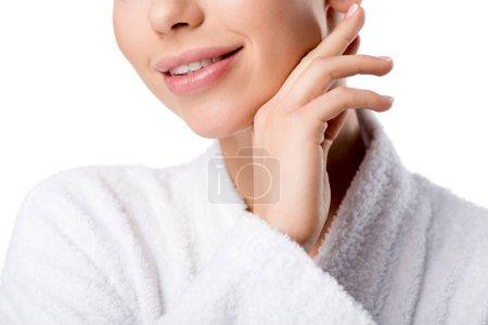 Photo pour Vue partielle de la femme souriante en peignoir touchant le visage isolé sur blanc - image libre de droit