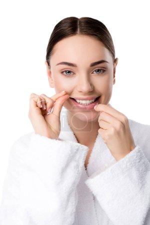 Photo pour Femme en peignoir blanc soie dentaire et regardant la caméra isolée sur blanc - image libre de droit