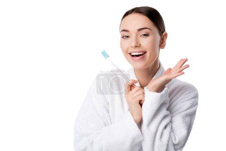 Photo pour Femme gaie en peignoir blanc tenant brosse à dents et regardant la caméra isolée sur blanc - image libre de droit