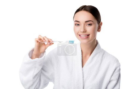 smiling woman in white bathrobe holding toothbrush and looking at camera isolated on white