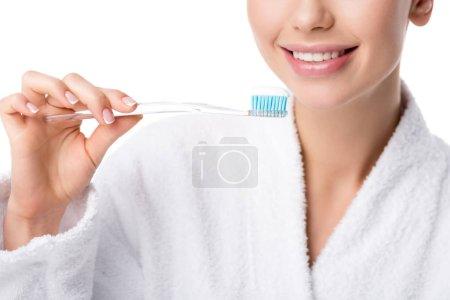 Photo pour Vue recadrée de la femme en peignoir blanc tenant la brosse à dents isolée sur blanc - image libre de droit