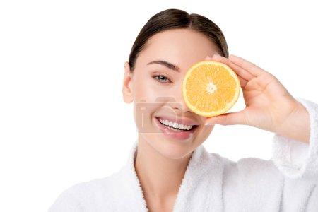 Photo pour Belle femme en peignoir blanc tenant orange face et regardant la caméra isolé sur blanc - image libre de droit