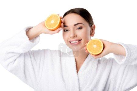 Photo pour Belle femme souriante en peignoir blanc tenant des oranges et regardant la caméra isolée sur blanc - image libre de droit