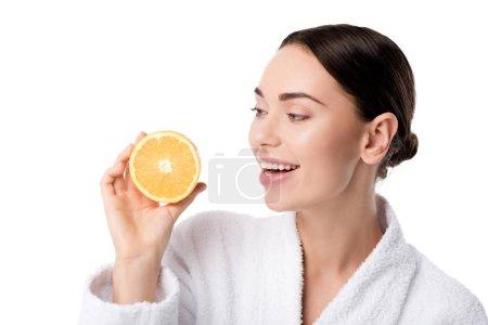 Photo pour Belle femme souriante en peignoir blanc tenant orange isolé sur blanc - image libre de droit
