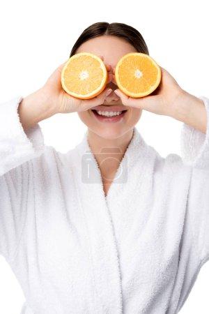 Photo pour Femme souriante en peignoir blanc tenant oranges devant visage isolé sur blanc - image libre de droit