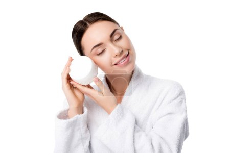 woman in bathrobe with eyes closed holding face cream isolated on white