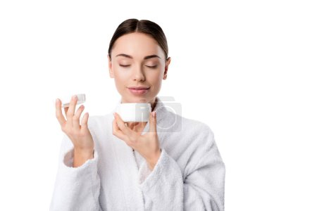 woman in bathrobe with eyes closed smelling aroma of face cream isolated on white