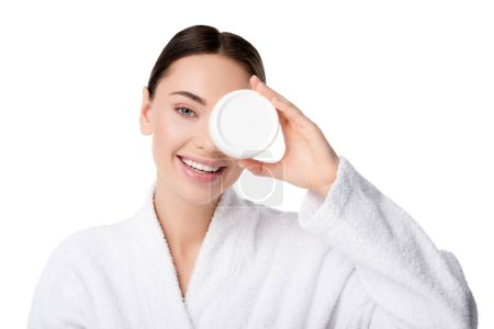 beautiful woman in bathrobe holding moisturizing cream in front of face isolated on white