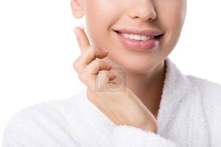 Photo pour Vue recadrée d'une femme souriante en peignoir avec crème visage à la main isolée sur blanc - image libre de droit