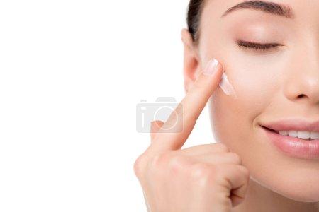 Photo pour Vue recadrée de la femme appliquant crème hydratante pour le visage isolé sur blanc - image libre de droit