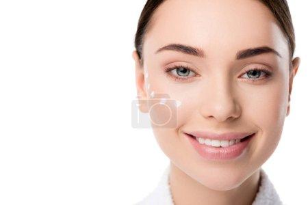Photo pour Belle femme souriante avec crème pour les yeux sur le visage en regardant la caméra isolée sur blanc avec espace de copie - image libre de droit