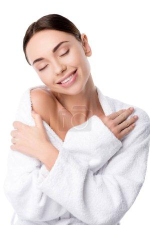 Photo pour Belle femme souriante en peignoir avec les mains croisées et les yeux fermés isolés sur blanc - image libre de droit